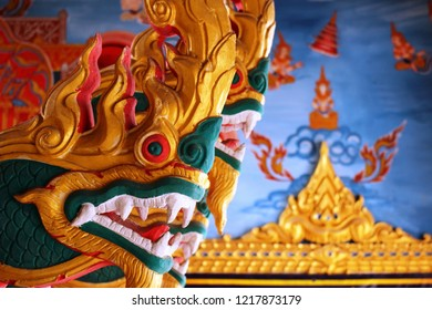 Carved wooden golden dragon statue in a Thai temple with Buddhist scene painted on a wall blurred in the background