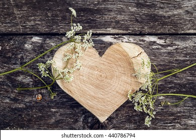 Carved wooden heart and white flower on a background of old boards. Place for text. Top view.