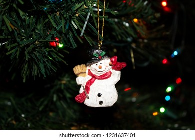 Carved Wooden Snowman Ornament with a Cardinal on his Shoulder hanging on a Christmas Trree