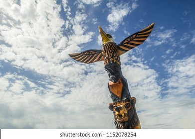 carved wooden totem pole with an eagle, a crow and a bear in Alaska