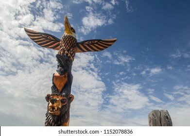 a carved wooden totem pole showing an eagle, a crow and a bear in Alaska