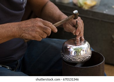 Carver carving a silver betel bowl with delicately