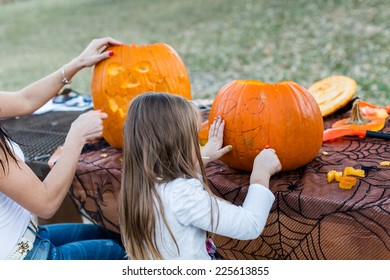 Carving big orange pumpkins for Halloween in late Autumn.