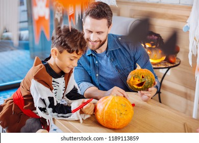 Carving and coloring. Beaming bearded father and handsome cute son feeling amazing while carving and coloring Halloween pumpkins
