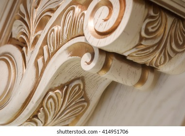 carving element. furniture in classic style. white color wood with gold trim. patina. carving. small depth of field. luxury furniture. use as background.