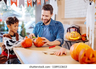 Carving pumpkin. Cute beaming son wearing Halloween costume feeling cheerful while carving pumpkin with his father