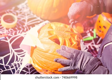 Carving pumpking outdoors in cold weather.