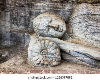 A carving of a reclining Buddha rests his head on a stone pillow in the historic ancient city of Polonnaruwa in Sri Lanka.
