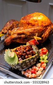 Carving roasted herb rubbed turkey garnished with fresh grapes, oranges, and cranberry is ready for Christmas dinner.