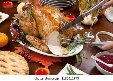 Carving roasted pepper turkey for Thanksgiving, garnished with pink pepper, blackberry, and fresh rosemary twigs on a dinner table decorated with mini pumpkins, beans, carrots, candles