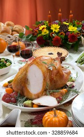 Carving roasted turkey on a server tray garnished with fresh figs, grape, kumquat, and herbs on fall harvest table. Red wine, side dishes, pie, and gravy.
