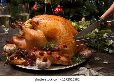 Carving rustic style roasted Christmas turkey garnished with roasted garlic, lemon, and rosehips. Surrounded with rustic Christmas ornaments, candles, wine, flowers, and Christmas tree