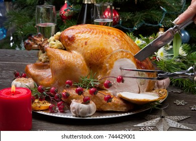 Carving rustic style roasted Christmas turkey garnished with roasted garlic, lemon, and rosehips. Surrounded with rustic Christmas ornaments, candles, wine, flowers, and Christmas tree.