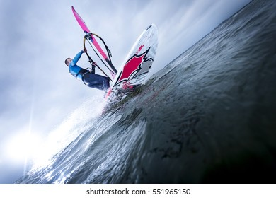 carving of a windsurfer at an open lake