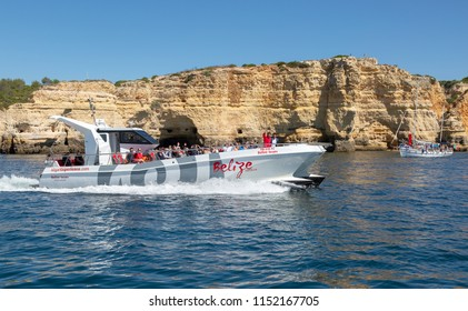 CARVOEIRO, PORTUGAL- July 27th, 2018: Fast  boat from Portimao taking tourists around the coast near Carvoeiro to visit the caves