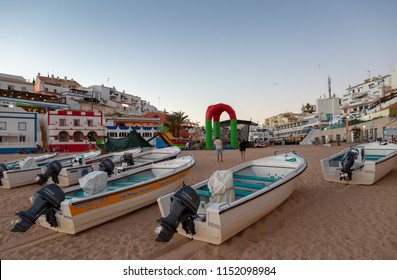 CARVOEIRO, PORTUGAL- July 29th, 2018: Early evening view of cave tour boats on the beach with Carvoeiro town square behind.