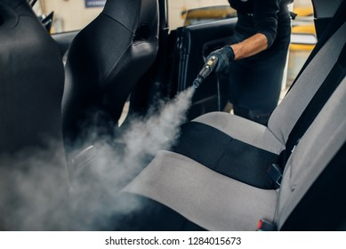 Carwash, worker cleans seats with steam cleaner