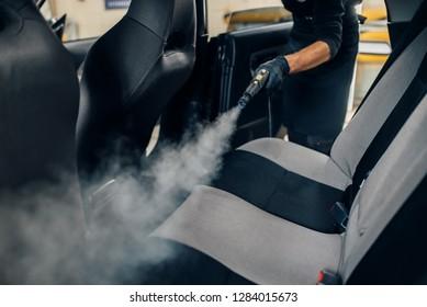 カーウォッシュ、作業者は蒸気クリーナーで座席を掃除する