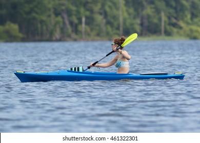 CARY, NORTH CAROLINA - JUL 30: Young woman in bikini enjoys her kayak workout in the hot weather on 30 July 2016 at Lake Jordan