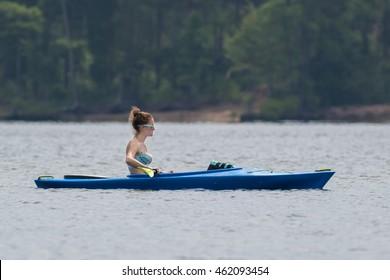 CARY, NORTH CAROLINA - JUL 30: Young woman in bikini takes a break in her kayak workout on 30 July 2016 at Lake Jordan