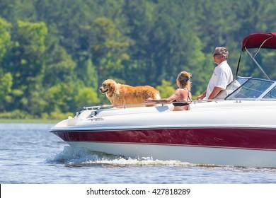 CARY, NORTH CAROLINA - MAY 28: Young family with dog enjoying a boat ride on 28 May 2016 at Lake Jordan