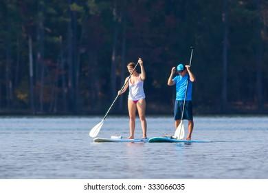 CARY, NORTH CAROLINA - OCT 24: Young couple getting a paddle board workout on 24 Oct 2015 at Lake Jordan