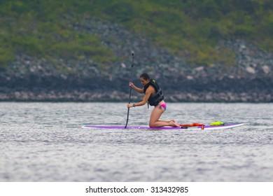 CARY, NORTH CAROLINA - SEPT 5: Stand up paddle boarder finishing a long workout on 5 Sept 2015 at Lake Jordan
