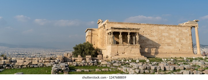 The Caryatid Porch visible as part of the ancient Erechtheion Temple in the Acropolis, in Athens, Greece, with the cityscape beyond.
