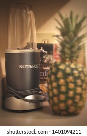 Cary,NC/US-May 18 2019 Nutribullet on the kitchen counter with a pineapple and recipe book waiting to make tasty treat.