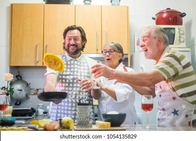 carzy moment funny group of middle age man and two senior man and woman. omelette flying during the cook f the dinner. kitchen play together