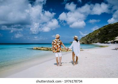 Cas Abou Beach Curacao on the caribbean island of Curacao, Playa Cas Abou in Curacao Caribbean tropical white beach with blue ocean men and woman on the beach, couple mid age on vacation