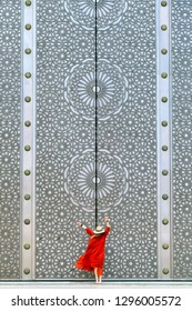 Casablanca / Morocco - 2017-05-09; A girl in a long red dress and a hat is dancing near a huge door with symbols of sacred geometry.