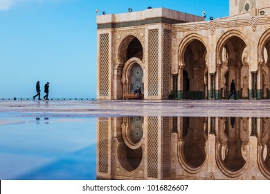 Casablanca, Morocco - January 28, 2018 : view of Hassan 2 mosque square reflected on water and two people walking