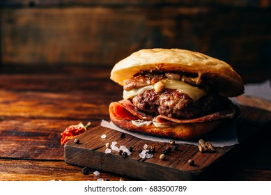 The Casanova Burger on Cutting Board. Cheeseburger with Beef Patty, Wisconsin Swiss Cheese, Ham, Sauteed Mushrooms, Dijon Mustard, Mayonnaise and Potato Roll. Wooden Background and Copy Space.