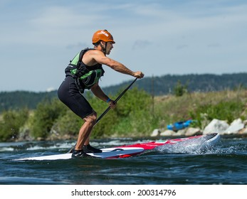CASCADE, IDAHO/USA - JUNE 21, 2014: Stand up Paddle boarder  driving to the finish at the Payette River Games