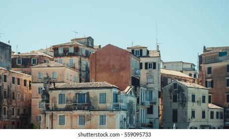 Cascade of peeling old mediterranean houses against clear blue sky - Corfu, Greece