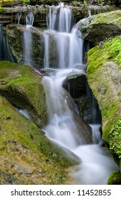 A cascade of water flows down and around moss covered rocks.
