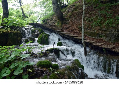 Cascade waterfalls under wooded pavement, in Plitvice Lakes National Park (Nacionalni park Plitvicka jezera). Karlovac County, Croatia.