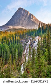 Cascading Grassi Lakes Waterfall in the Kananaskis Country of Alberta near Canmore with afternoon sun shinning on Ha Ling Peak in the background.