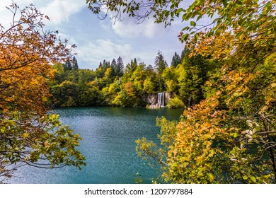 Cascading Plitvice lakes in Croatia on a cloudy warm day. Red orange leaves of autumn trees are reflected in the green water. The concept of ecological, active and phototourism