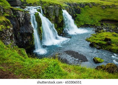 Cascading waterfall Kirkjoufellfoss at the foot of the mountain Kirkjoufell. Summer in Iceland. Concept of exotic and extreme tourism