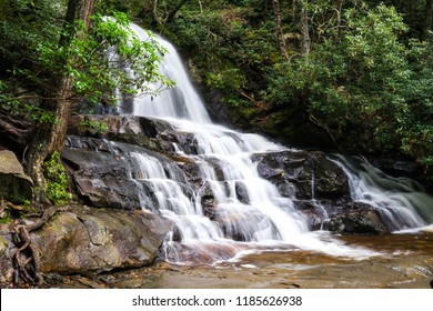 Cascading waterfall in mountains surrounded by forest; scenic outdoor landscape background