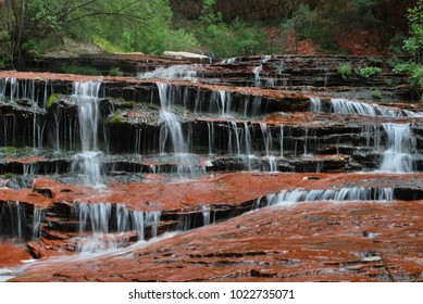 Cascading waterfall over layered sandstone in Zion National Park