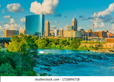 The cascading White River and the skyline of Indianapolis, Indiana both glow in the last light of the day.