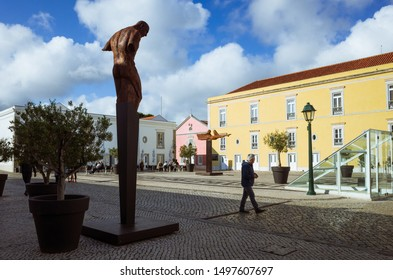 Cascais, Lisbon district, Portugal - May 28th, 2018 :  A man walks past an Iron sculpture by Rogerio Timoteo at the Cidadela Art District inside the Citadel of Cascais.