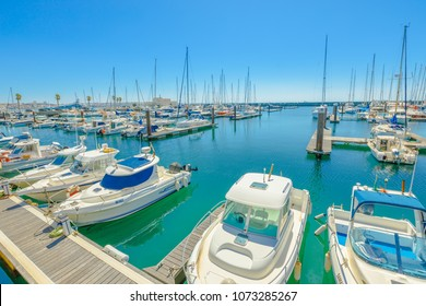 Cascais, Portugal - August 6, 2017: yacht and motor boats docked at Cascais marina. The Marina is located under Cascais Cidadela. Summer holidays in sunny day. Turquoise bay. Blue sky with copy space.