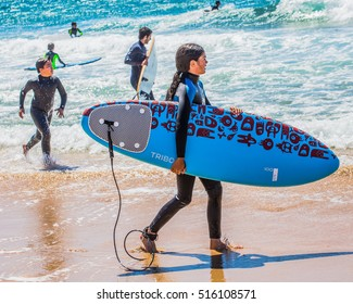 CASCAIS, PORTUGAL,  JUNE 20, 2016 - Young girl in wetsuits with a surfboard on a sunny day at the beach