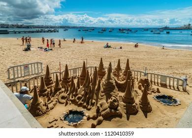 Cascais, Portugal - June 9, 2018: Man builds a sand castle on Praia da Ribeira beach in Cascais, Portugal