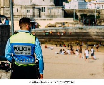 Cascais, Portugal - May 16, 2020: Police officer on vigilance next to a beach to ensure respect for social distancing during the Coronavirus Covid-19 epidemic in Portugal