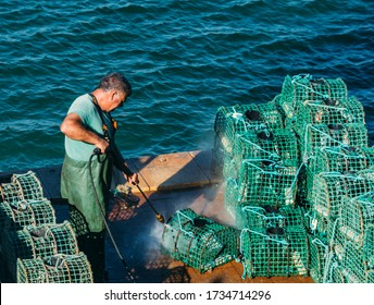 Cascais, Portugal - May 18, 2020: Man cleans fishing cages or traps on a sunny day in Cascais, Portugal